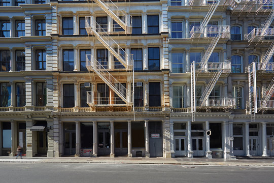 New York building facades with fire escape stairs and empty street