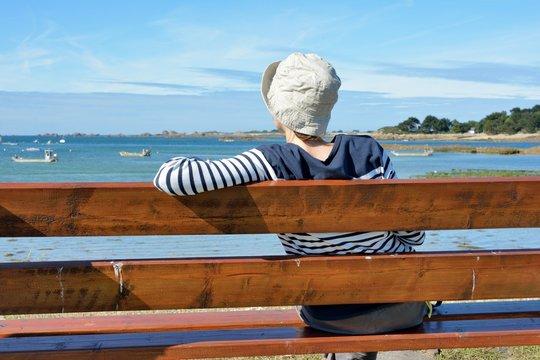 Une jeune femme habillée d'un pull marin est assise sur un banc face à la mer
