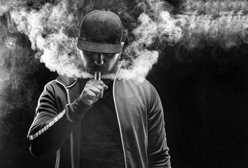 vaping man holding a mod. A cloud of vapor. Black background