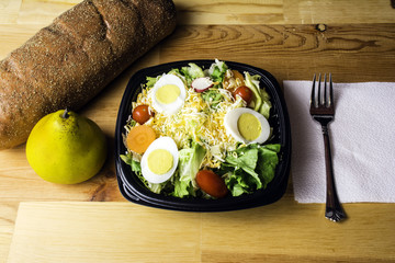 fresh garden salad of lettuce tomato radish carrot cheese and egg on wood background