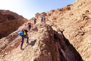 Group backpackers ascending climbing desert mountain trail lifestyle.