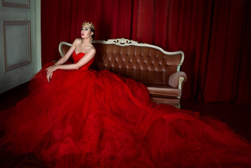 Beautiful girl in long red dress and in royal crown sitting on the retro sofa  on red background in photo studio