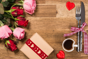 Roses, fork, knife, coffee and gift on wooden background. Valentines day background