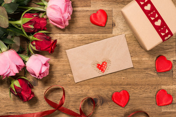 Roses, gift, red hearts and message card  on wooden background. Valentines day background