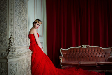 Beautiful girl in long red dress and in royal crown near fireplace in luxury interior in photo studio