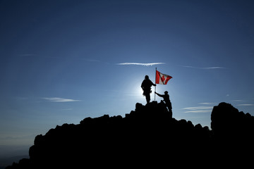 Two soldiers raise the Canadian flag on a mountain top