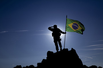 Soldier on top of the mountain with the Brazilian flag