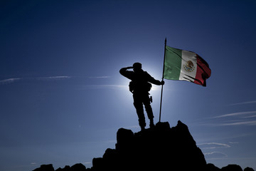 Soldier on top of the mountain with the Mexican flag