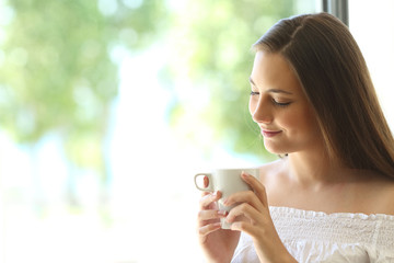 Romantic girl thinking and looking at coffee cup
