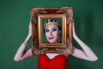 Beautiful girl in long red dress and in royal crown with golden picture frame