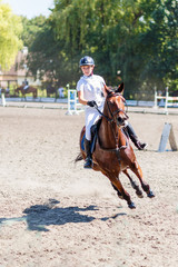 Young rider girl on bay horse on equestrian competition at hot summer day