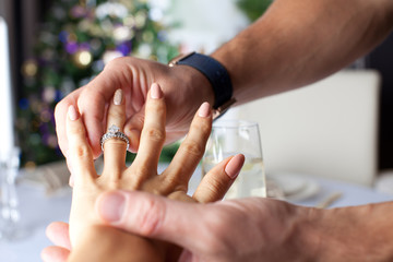 Elegant man putting engagement ring to his girlfriend hand.