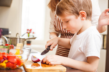 Small boy cooking together with his mother in the kitchen
