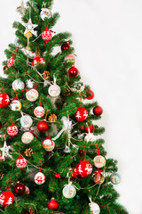 Christmas tree on a white background decorated with red and white balls