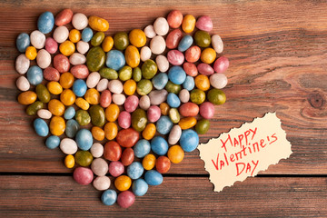 Colorful candy heart and card. Pile of sweet sea pebbles. Add sugar to your relationship.