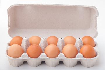 Ten dozen hen eggs in a paper container on a white background