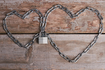 Chain hearts with lock. Metallic chain on wooden background. Hearts will be connected forever.