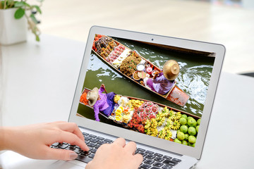 Hand of the woman using a laptop to find information of the Floating Market for a travel in Thailand. Thailand's famous floating market is Damnoen Saduak Floating Market and Amphawa Floating Market.