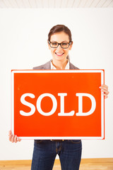 Realtor In Empty Apartment, Holding 'sold' Sign