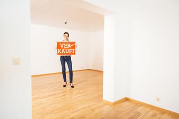 Realtor In Empty Apartment, Holding 'verkauft' Sign