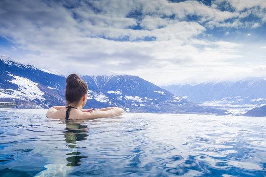 Frau geniesst Bergpanorama im Winter vom Pool aus
