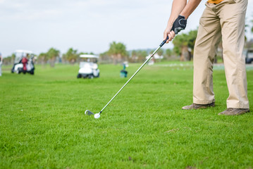 Business man holding golf club playing on grass field background. Active male outdoors