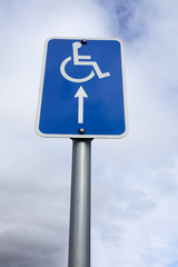 Handicapped wheelchair  sign with arrow pointing up into grey / gray sky. Vertical.