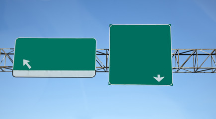 Two blank green interstate highway sign with arrows against blue sky. Horizontal.