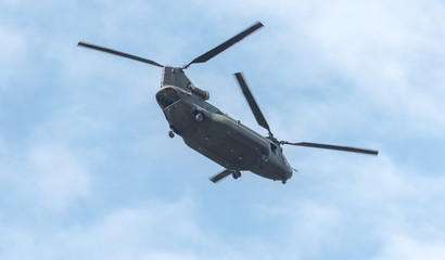 Double rotor, heavy airlift, military helicopter in flight with rear ramp door open.