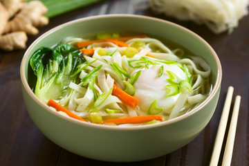 Vegetarian Asian rice noodle soup with bok choy, carrot, spring onion and a poached egg, photographed with natural light (Selective Focus, Focus in the middle of the soup)