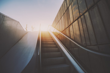 Outdoor city escalator stairway, under evening sun, with tiled rusty concrete wall on the right, wide view from bottom, rubber rail, vintage color filter