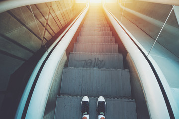 Outdoor city escalator stairway down, feet of guy in gumshoes ready to go down; evening sun, with tiled concrete wall on the left, wide view from above, vintage color filter
