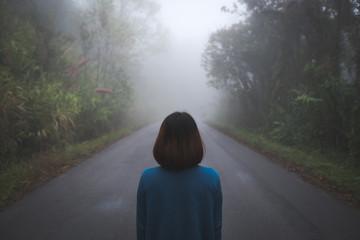 Woman on foggy road Fototapete