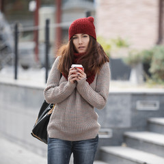 Young beautiful girl Asian appearance on the streets in the warm red cap and a scarf with a cup of coffee.