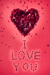 I love you and glitter red heart on pink background. Valentine's Day.