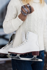 Cropped shot of a young woman standing with her ice skates slung over her shoulder