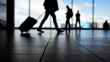 Travellers in airport walking to departures by escalator in front of window, silhouette