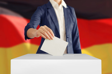 Voting. Woman putting a ballot into a voting box with German flag on background.
