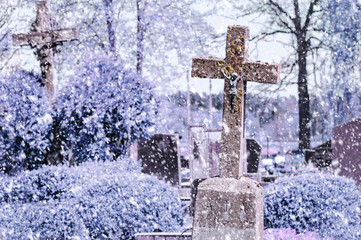 Concrete cross with crucifix in cemetery in winter