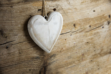 White heart shape made of wood hanging on a rustic wooden wall