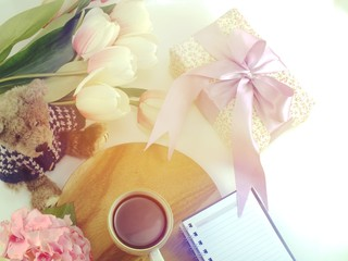 top view of morning coffee mug notebook with flowers and scarf on copy space white background