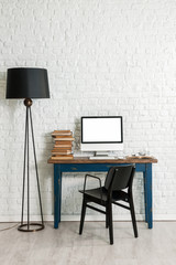 white brick wall concept and black lamp and black chair with computer interior decoration