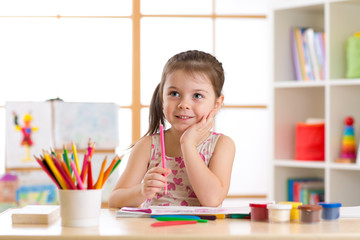 Preschooler child drawing and coloring by pencils
