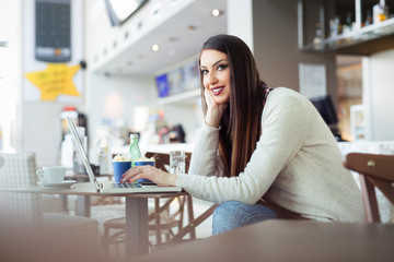 Freelance young woman sitting in the cafeteria with laptop and using mobile phone