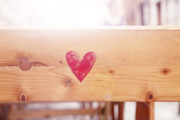 Red colored heart shape on wooden bench with sunlight and copy space background.