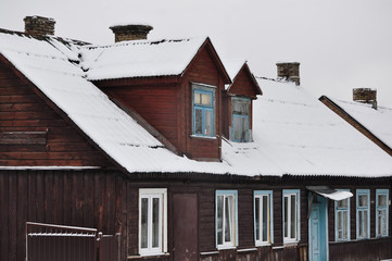 The old wooden houses with sloping roofs covered with snow after a snowfall.