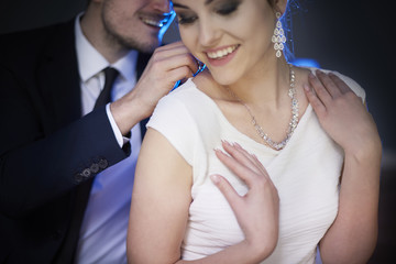 Smiling man giving woman elegant necklace .