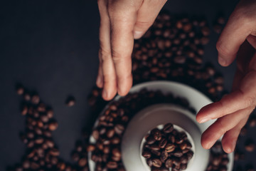coffee beans, black background, cup, saucer  coffee beans in hand