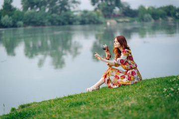 girl on the bank of the river with a camera
