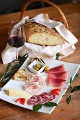 Mediterranean charcuterie snacks, antipasto with bread, wine, salumi, nuts, olives and pickles